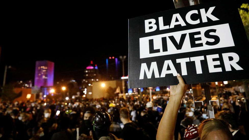 """A demonstrator holds up a """"Black Lives Matter"""" sign during a protest over the death of black man Daniel Prude, after police put a spit hood over his head during an arrest on March 23, in Rochester, New York, U.S. September 6, 2020"""