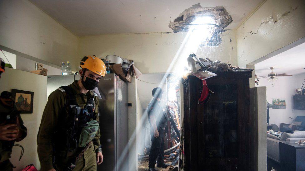 Tentara Israel bekerja di sebuah gedung yang rusak akibat roket yang diluncurkan dari Jalur Gaza, di Ashdod, Israel selatan 11 Mei 2021
