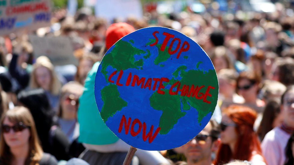 """Students hold up a sign with the slogan """"stop climate change now"""" during a protest in Vienna, Austria"""