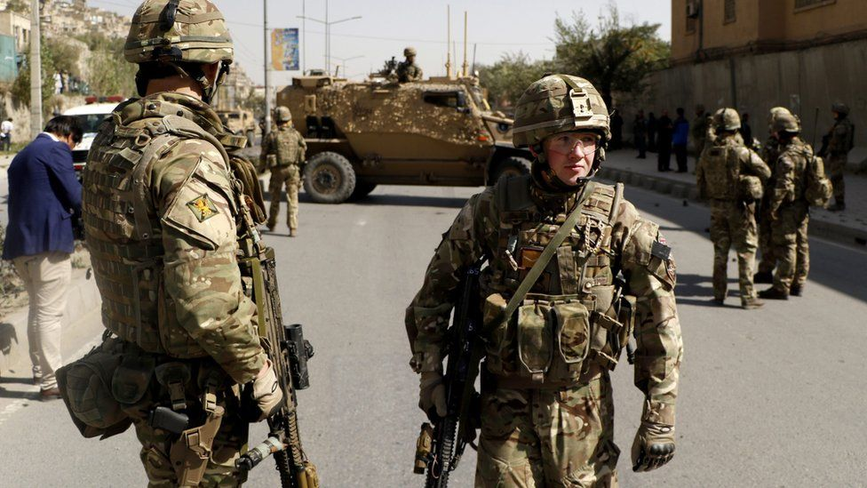 NATO soldiers inspect the scene of a suicide bomb attack in Kabul, Afghanistan, 11 October 2015