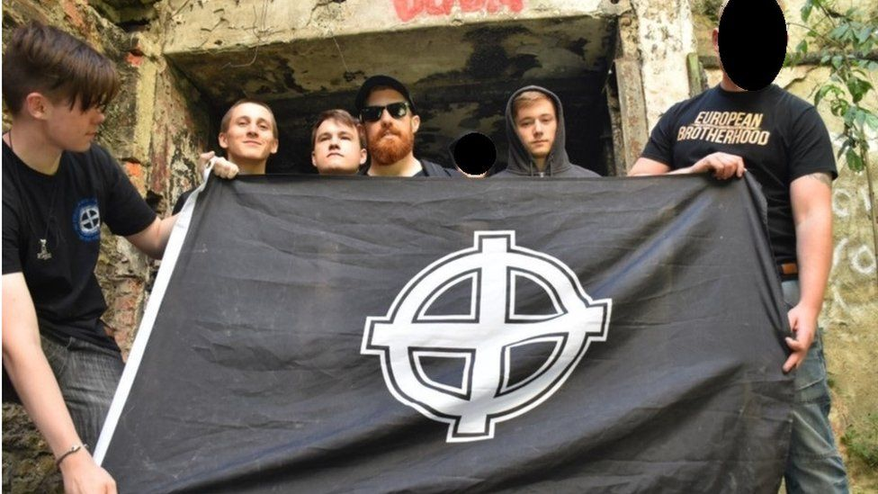 Hannam and others with Celtic cross, some faces blurred by Metropolitan Police