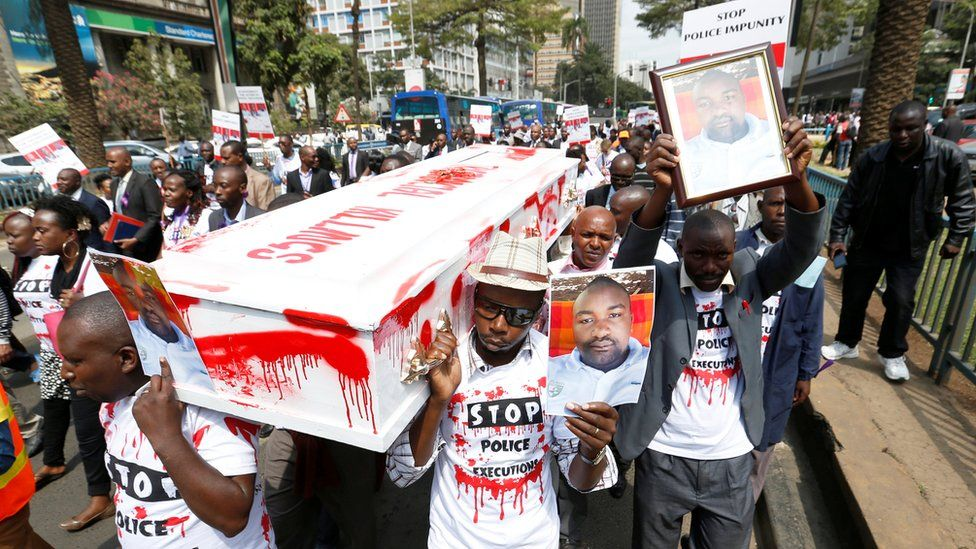 Protestors carrying a coffin smeared red paint