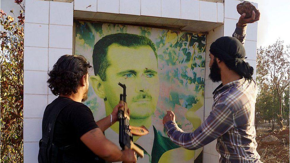 Syrian opposition fighters damage a portrait of Bashar al-Assad in Deraa (file photo)