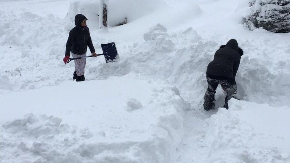 People dig out the path by their house after a snowfall in Erie, Pennsylvania. Photo: 26 December 2017
