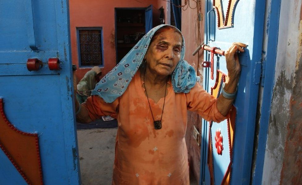 A bruised Asgari Begum, mother of 52-year-old Muslim farmer Mohammad Akhlaq, stands by the entrance of her home in Bisara, a village about 45 kilometers (25 miles) southeast of the Indian capital of New Delhi, Wednesday, Sept. 30, 2015.