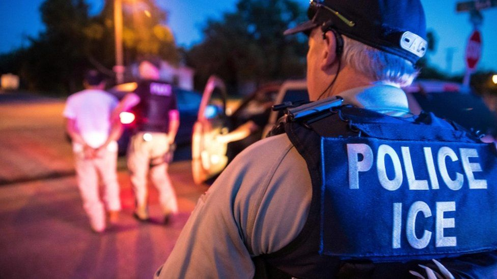 US Immigration and Customs Enforcement officers carry out a raid in Sherman, Texas, in June