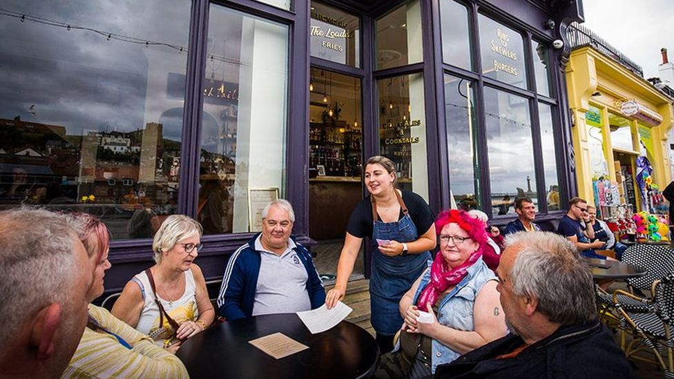 A group sits outside a bar and restaurant in Whitby