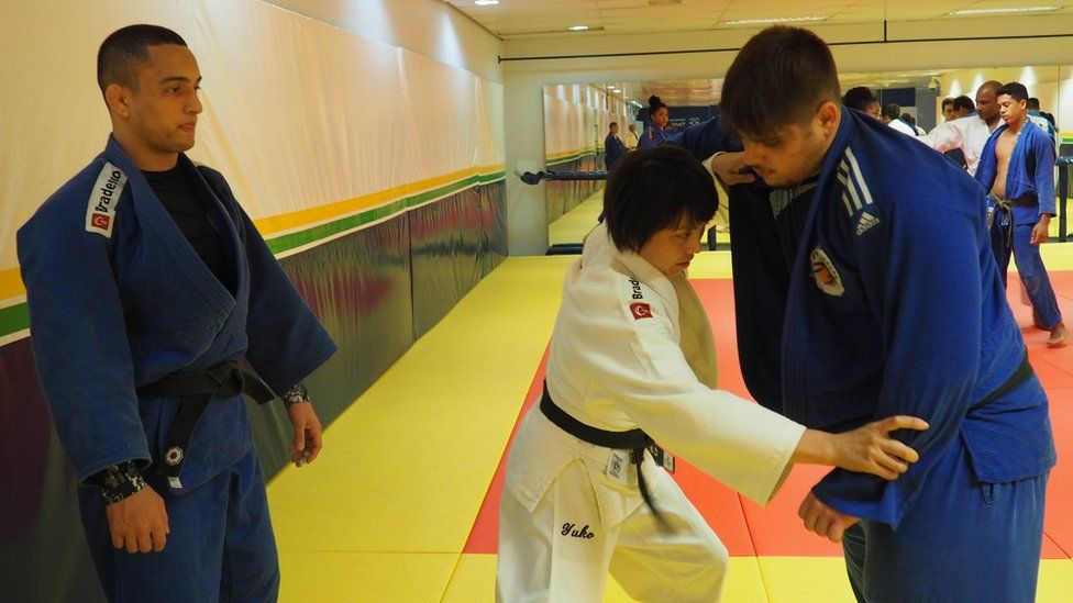 Yuko demonstrates a move while another team members looks on