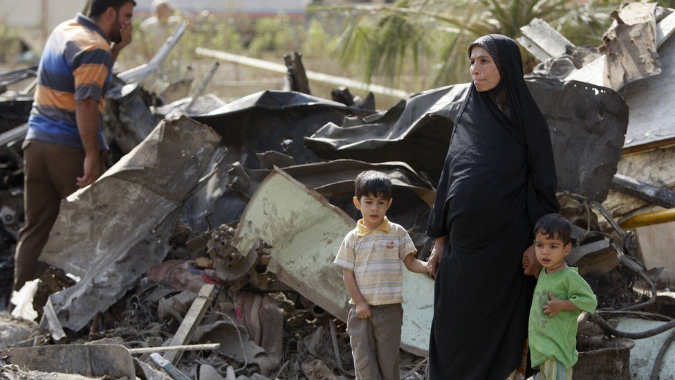 An Iraqi woman and her boys survey the damage after October 2009 bomb attacks in Baghdad.