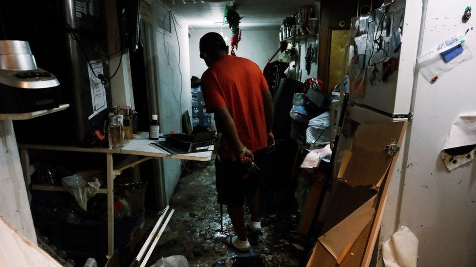 A resident walks through his flooded basement level apartment in a Queens neighbourhood