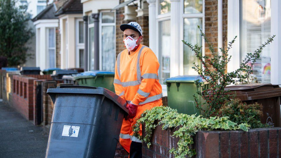 Refuse collector wearing a mask