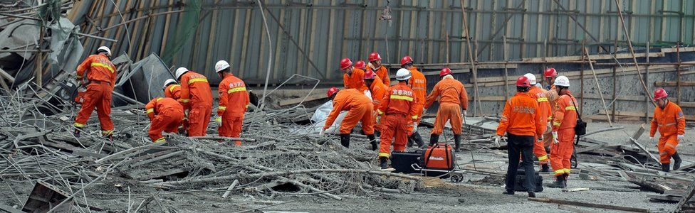 Workers search for survivors in the debris of a collapsed platform in a cooling tower at a power station at Fengcheng, in China's Jiangxi province
