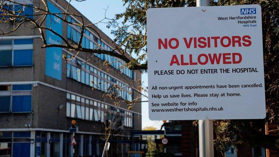 Sign saying no visitors allowed outside hospital