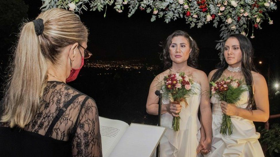 Alexandra Quiros (C) and Dunia Araya (R) stand before a lawyer during their wedding in Heredia, Costa Rica, on May 26, 2020
