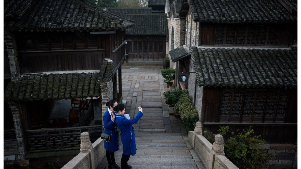 Two women take a selfie on a bridge in Wuzhen