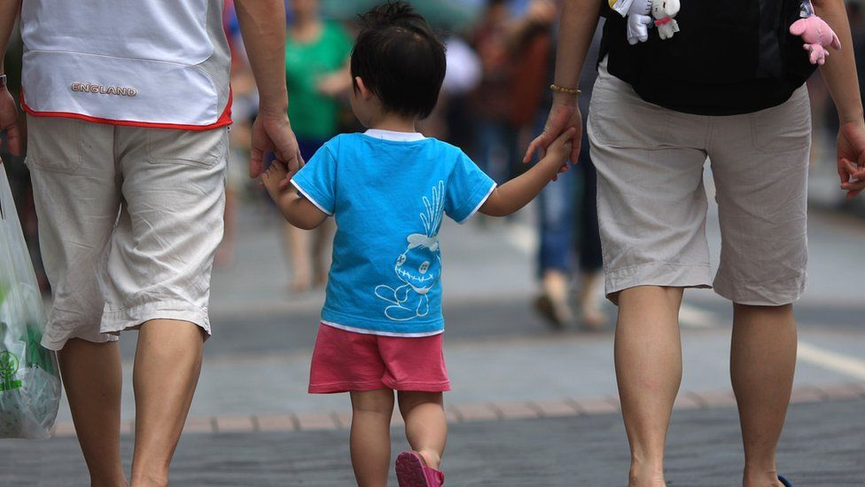 File photo: A Chinese family walking on a pavement