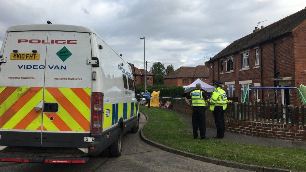 Police van and officers standing outside the scene of a house fire