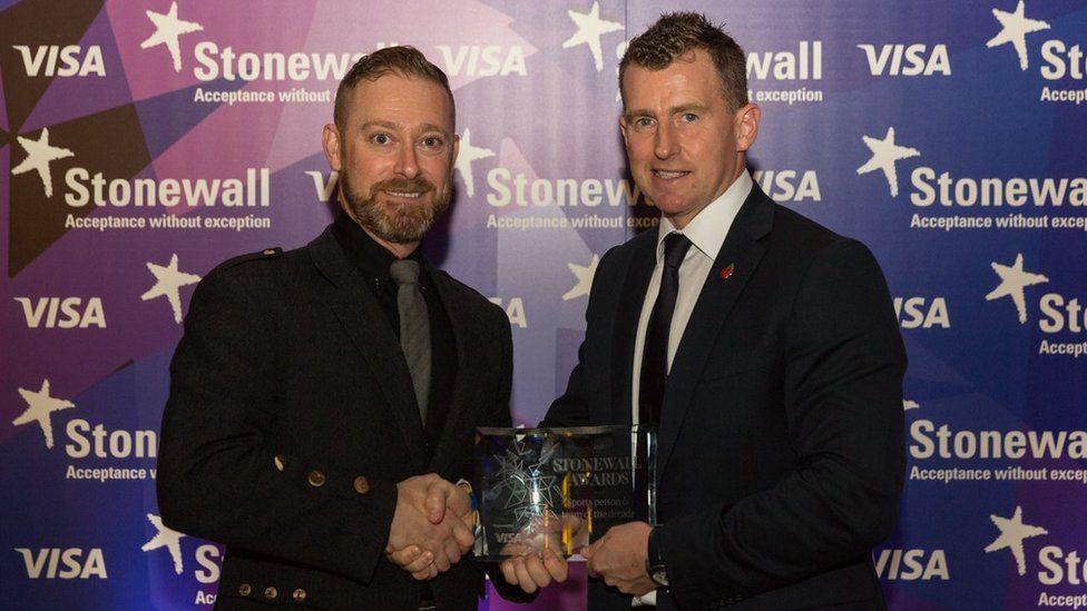 Nigel Owens (dde) yn derbyn ei wobr gan Cyfarwyddwr Stonewall Cymru Andrew White