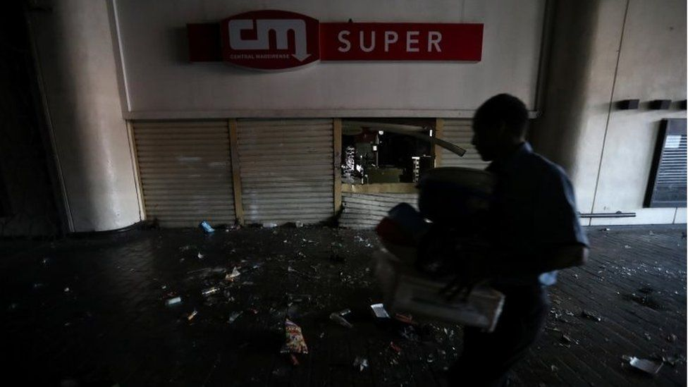 A shop employee helps clean up the area after the shop was looted during an ongoing blackout in Caracas, Venezuela, March 10, 2019.