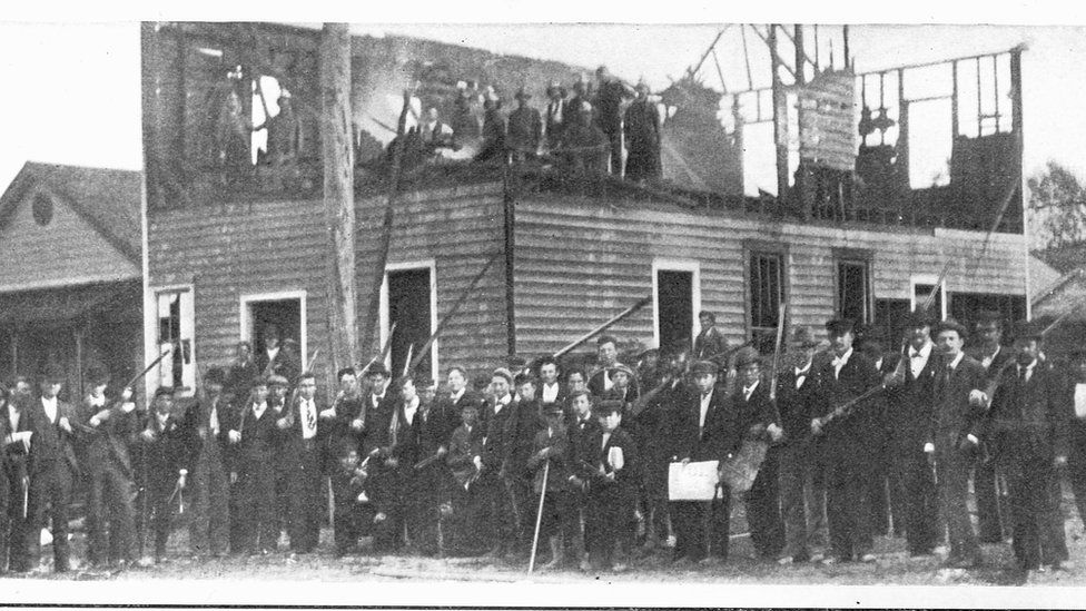 A mob stands outside the burnt offices of the Wilmington Daily Record