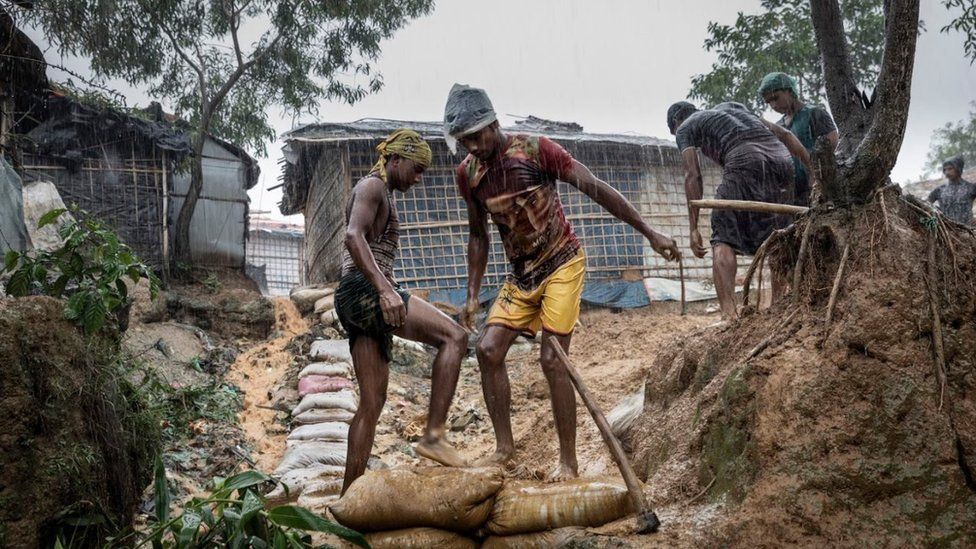 Men laying down sand bags