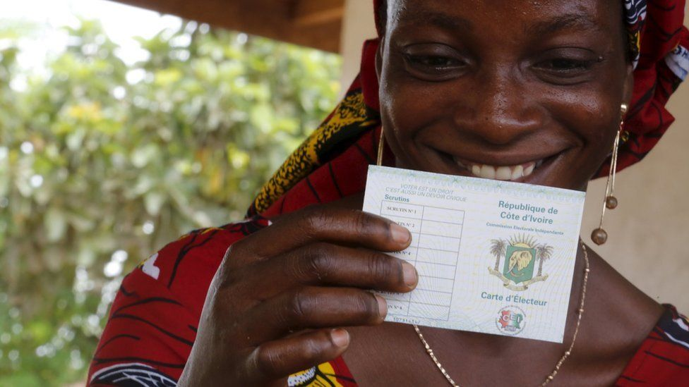 A woman smiles as she received her electoral card in Bingerville district, Abidjan