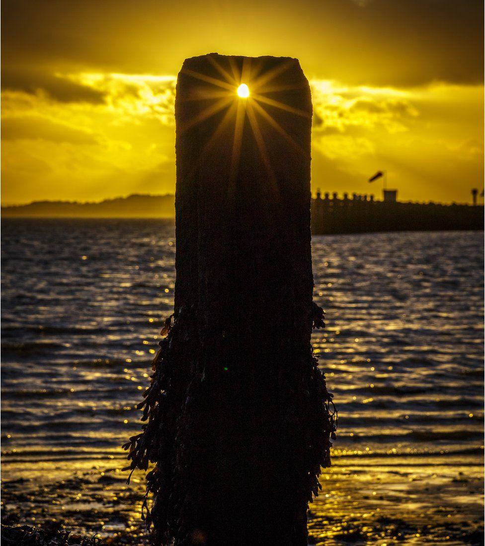 Sunset through harbour posts