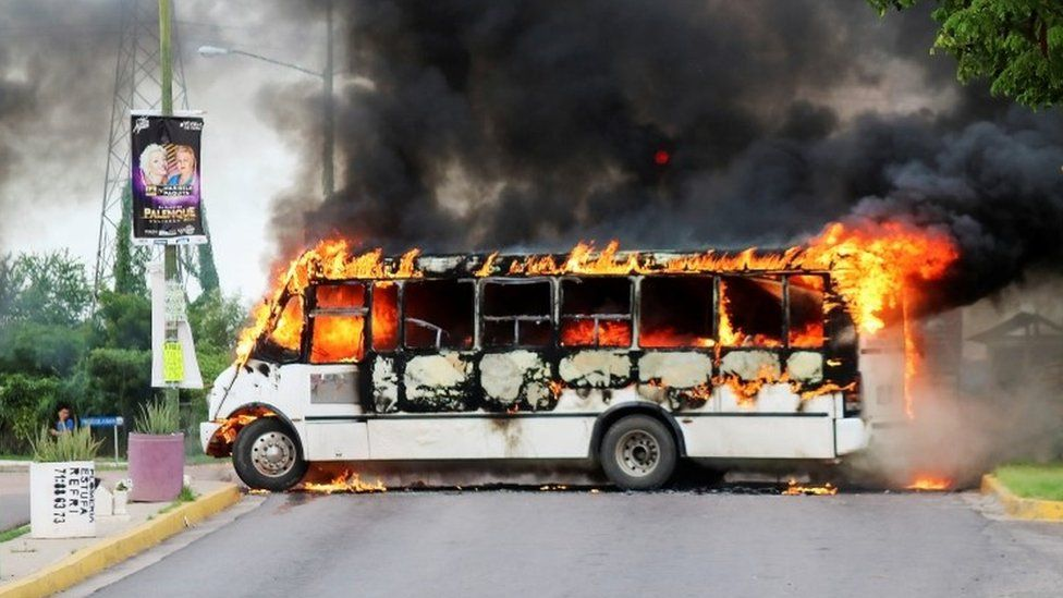A burning bus, set alight by cartel gunmen to block a road, is pictured during clashes in Culiacán