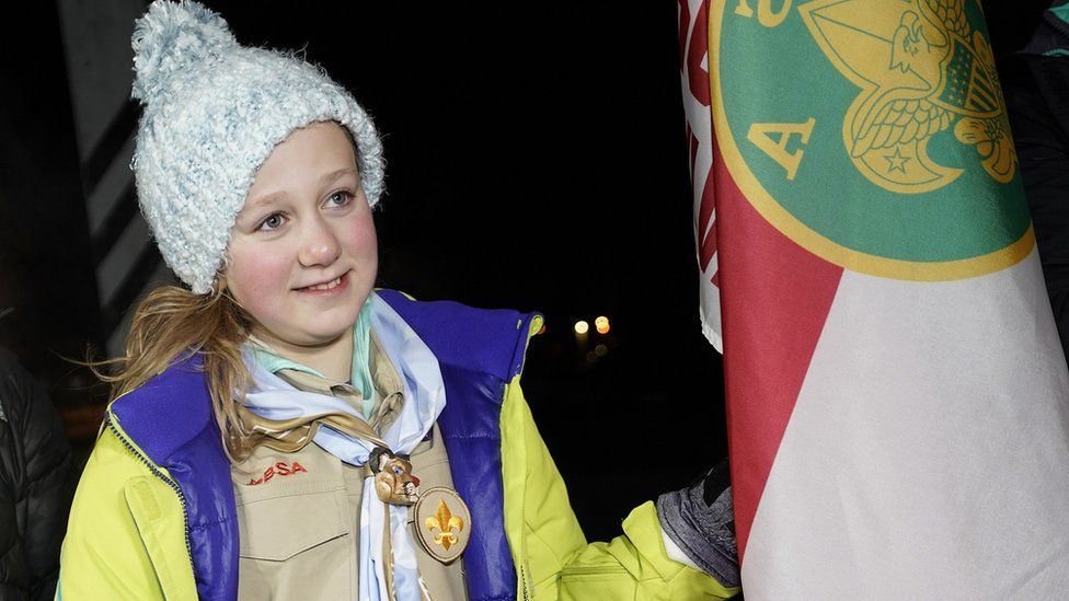 Vaughn stood next to her scout troop's flag