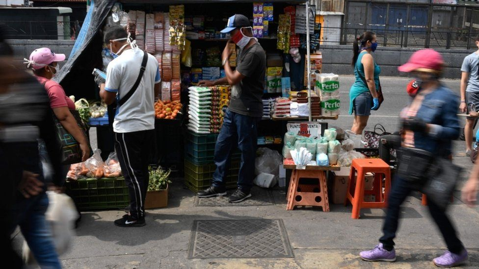 People wear face masks in a market as a preventive measure against the spread of the new coronavirus, COVID-19, at the Petare neighborhood in Caracas, on April 2, 2020