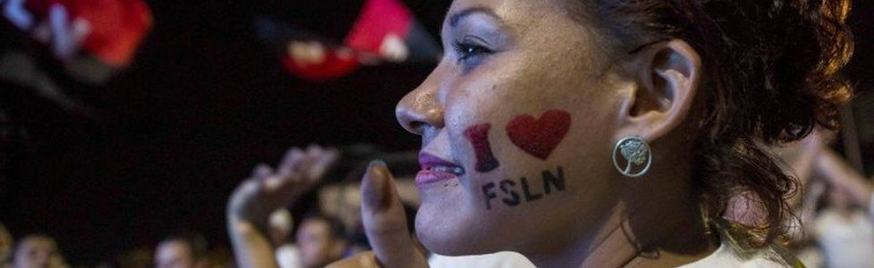 """A woman has a """"I love FSLN"""" painted on her cheek in Managua."""