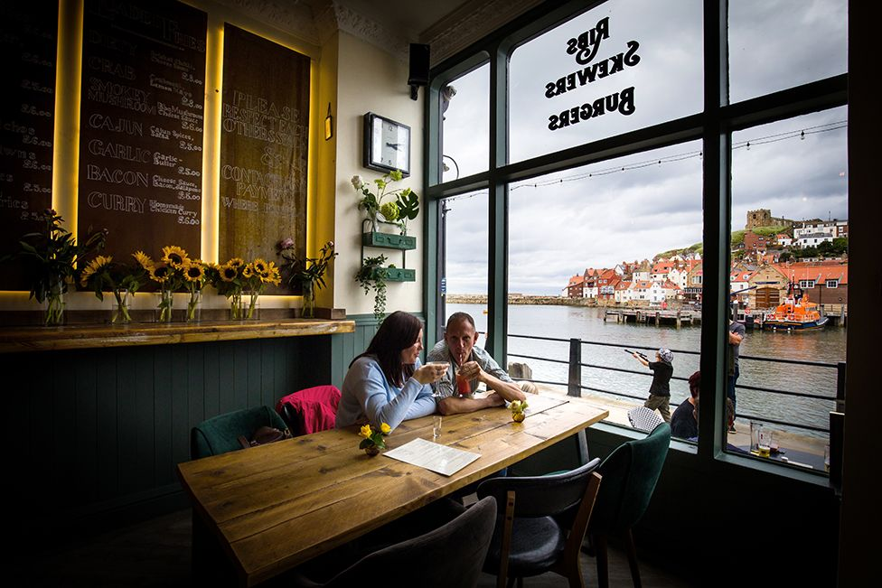 Emma Morley and Lee Clarke from Peterborough, drinking at The Moon and Sixpence, Whitby. 4 July 2020