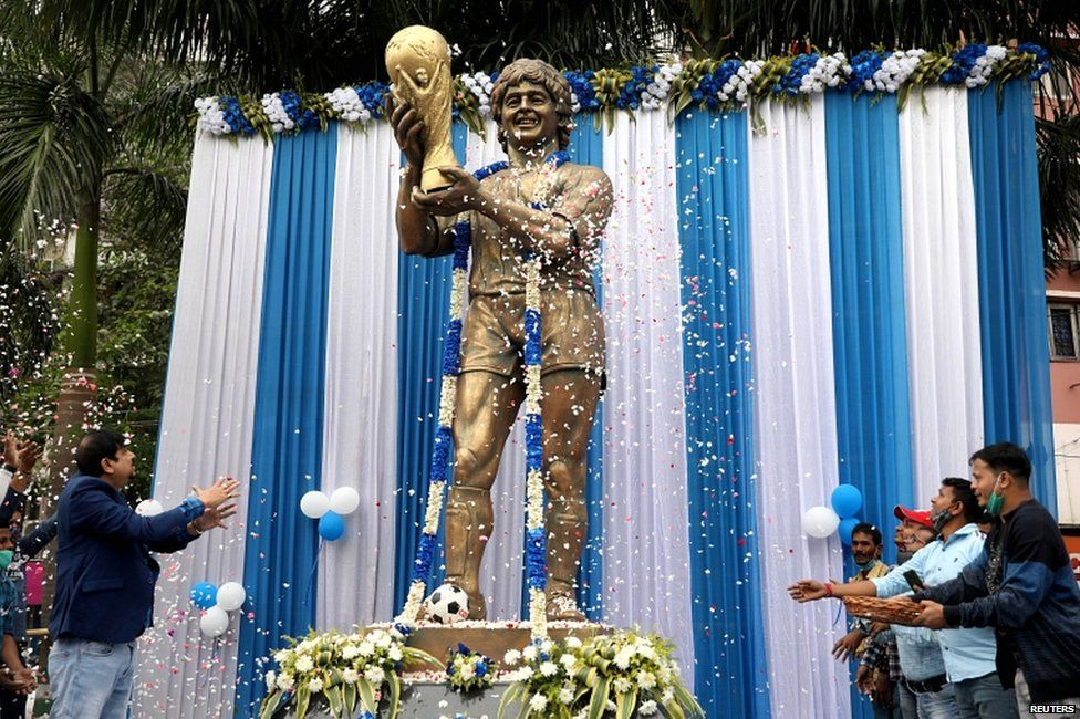 People shower petals on a statue of Argentine soccer great Diego Maradona during a prayer meeting to pay tribute to the player, in Kolkata, India, on 26 November 2020