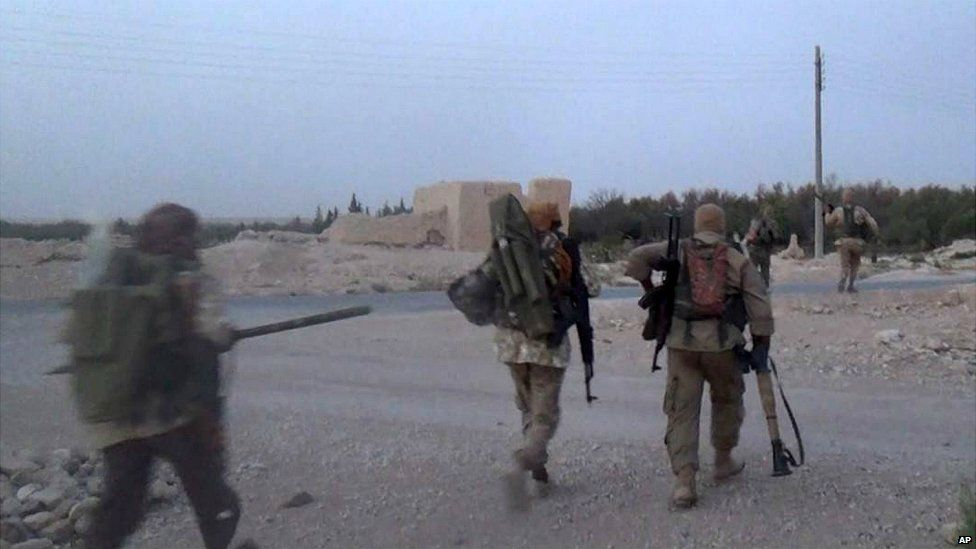 Islamic State militants carry their weapons in the town of Qaryatain, near Palmyra, in Syria - 5 August 2015