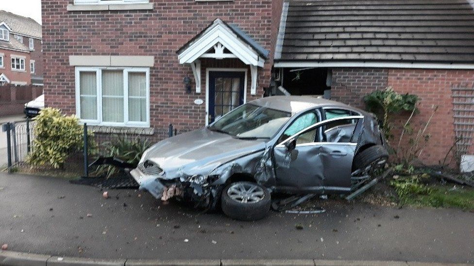 Smashed up car outside a house