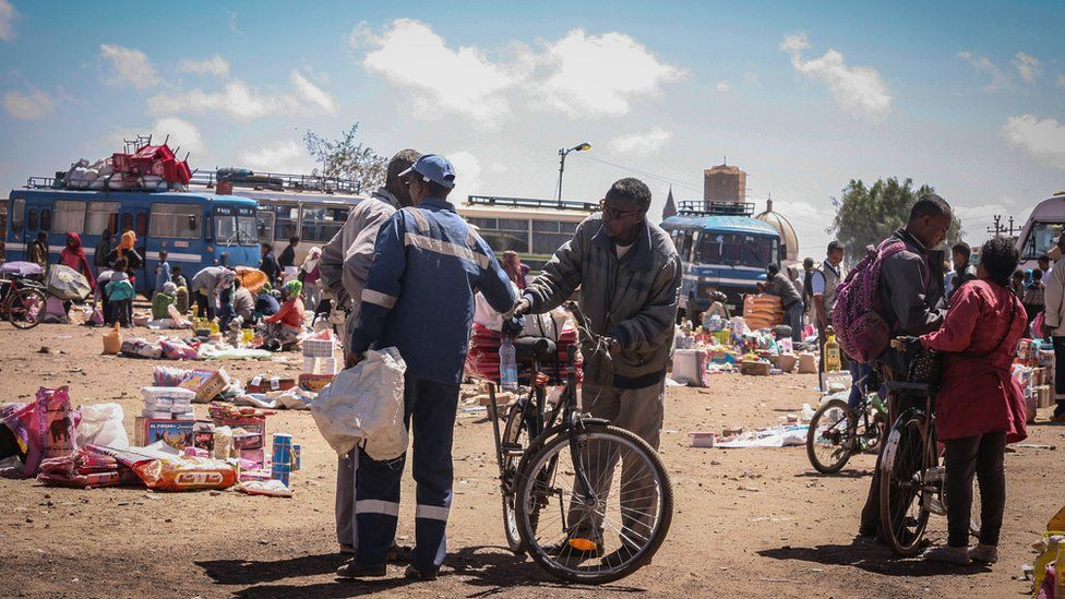 A bus station with old buses, markets traders and some people with bicycles in Asmara, Eritrea