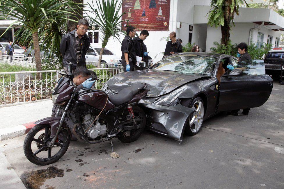 Policemen examine a damaged Ferrari at the home of the late Red Bull founder Chaleo Yoovidhaya in Bangkok, Thailand 3 September 2012.