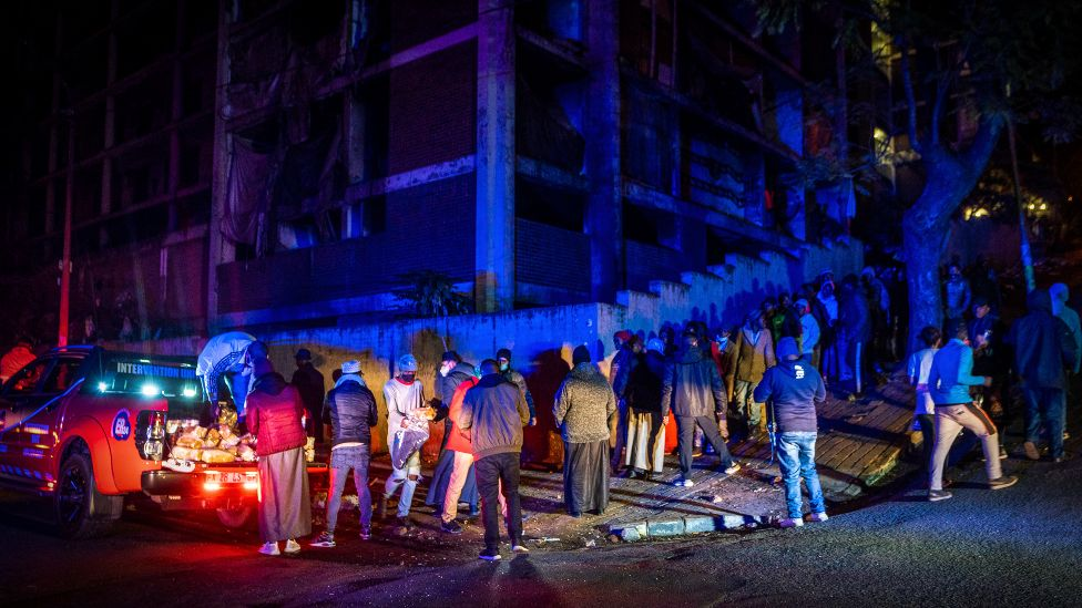 Residents of the derelict San Jose building in Johannesburg stand in line waiting to receive their share of bread, tinned food and a blanket from the Muslim Association of South Africa