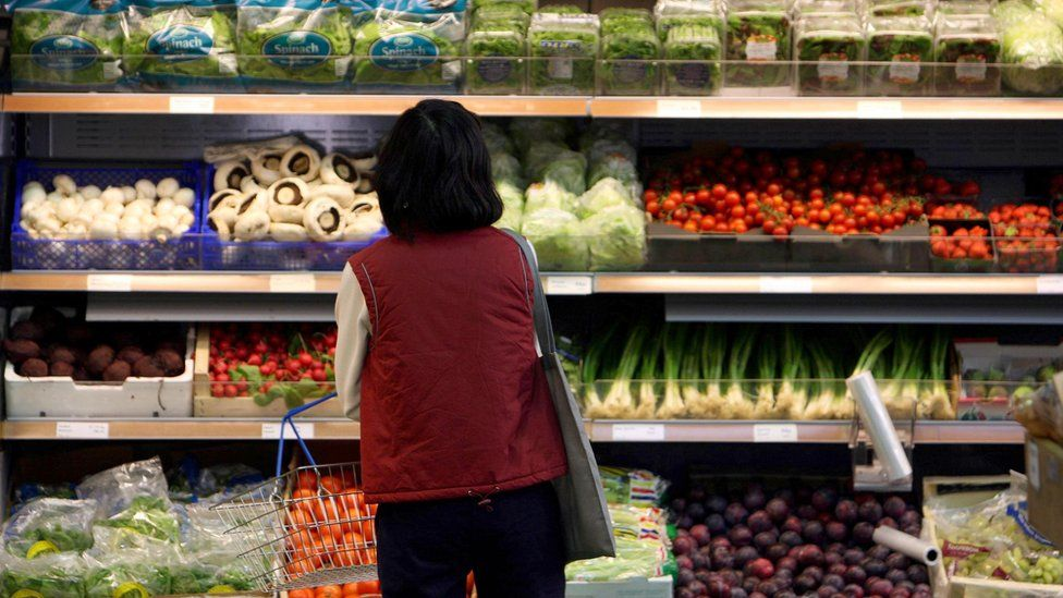 A customer looks at vegetables on display at a farm shop in Cambridgeshire