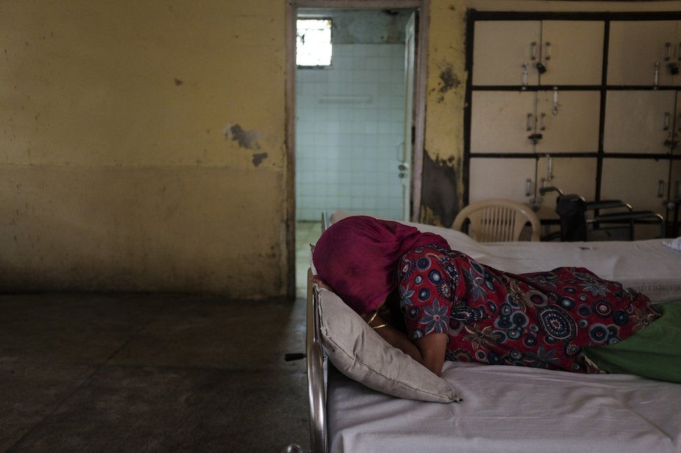 A young woman who developed psychotic symptoms after being gangraped is seen lying facedown on a bed in award at a mental health facility in Delhi. She was thrown out of her parent's home after she was diagnosed.