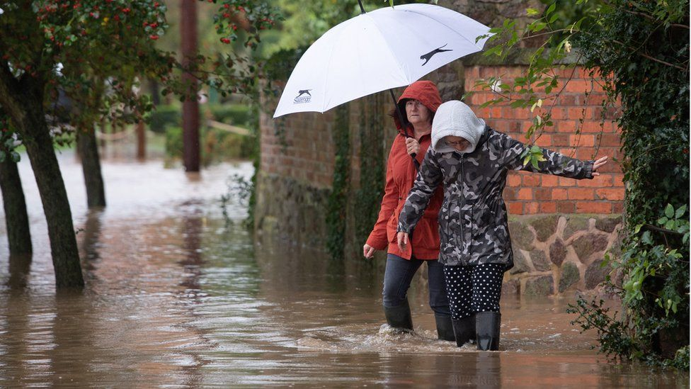 """Local residents make their way through floodwater in Cossington, Leicester after torrential thunderstorms and the village""""s proximity to the River Soar has seen parts of the village flooded"""