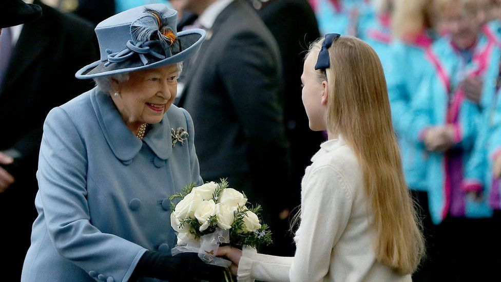 The Queen receiving a posy from an 11-year-old girl