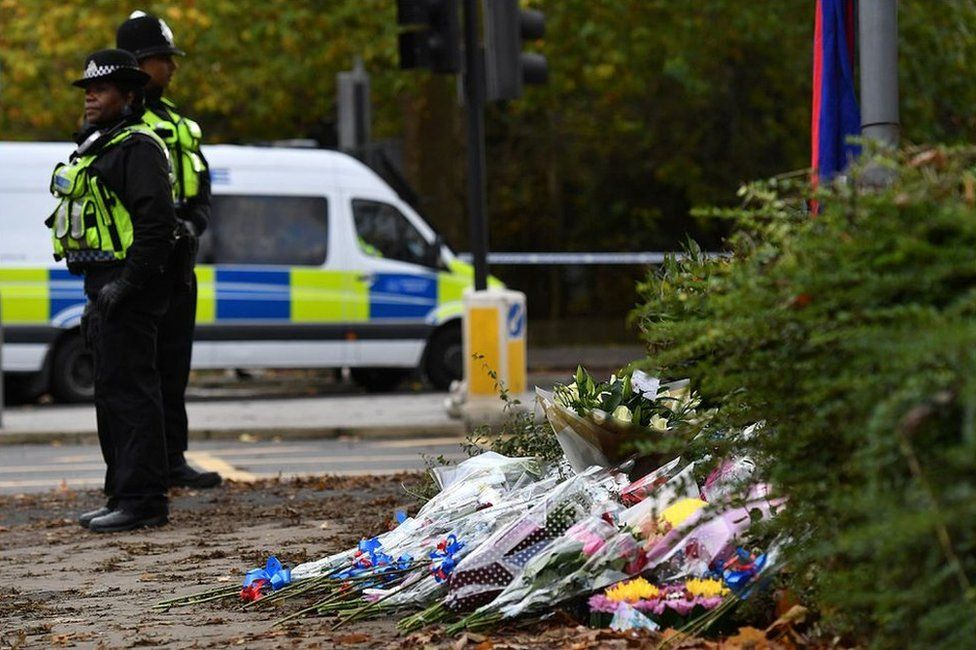 Police stand by flowers left near the scene of a derailed tram in Croydon