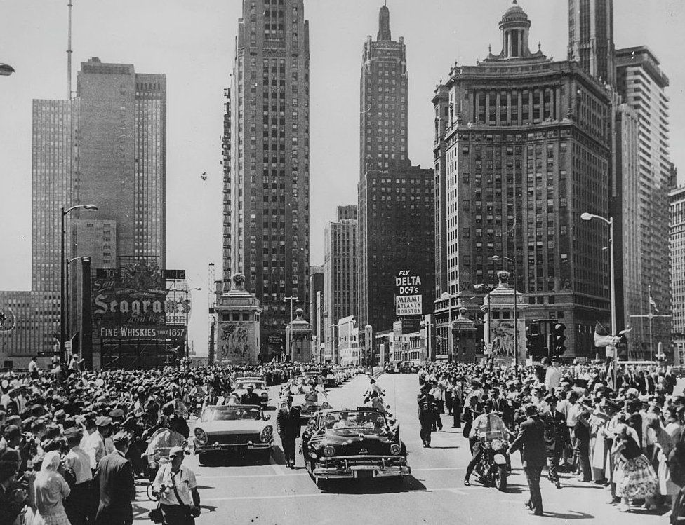 An open top car carries Queen Elizabeth II Prince Philip, Duke of Edinburgh north on Michigan Avenue, with the skyscrapers of the city of Chicago in the background, during a motor trip through the city after her arrival on the Royal Tour, 9 July 1959.