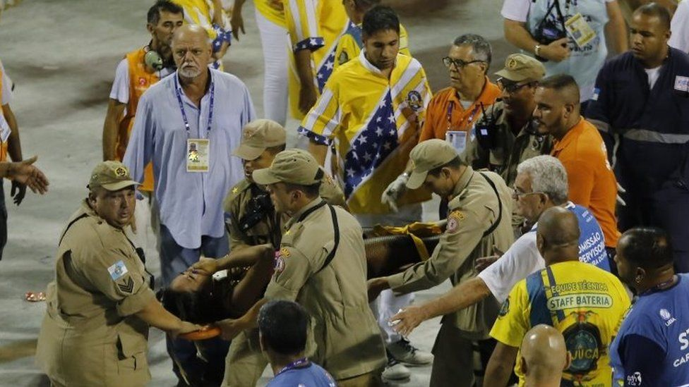 Firefighters carry an injured person on a stretcher to an ambulance during the performing of the Unidos da Tijuca samba school for the Carnival celebrations at the Sambadrome in Rio de Janeiro, Brazil, Tuesday, Feb. 28, 2017
