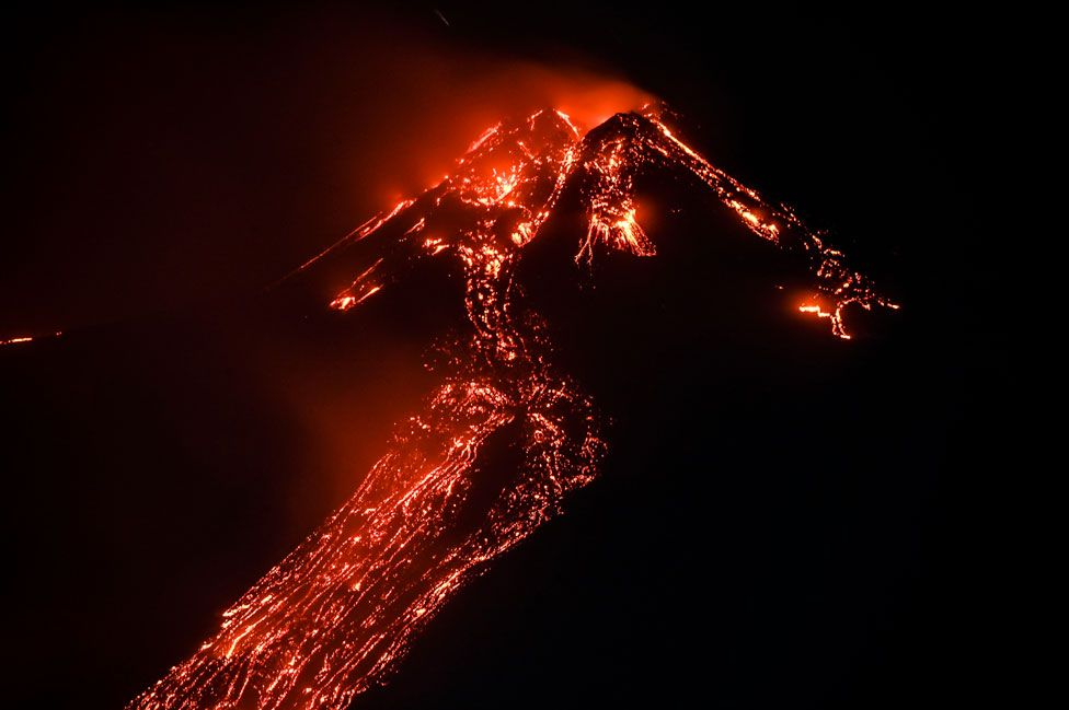 Lava flows down the side of Mount Etna at night