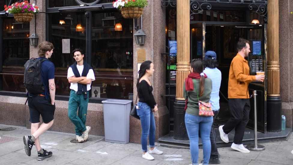 Customers queue outside a pub in east London