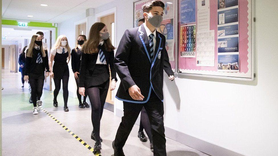 Masked pupils in school corridor