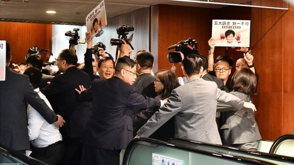 Security tries to control members of the press and protesting pro-democracy lawmakers after Carrie Lam had to leave the chamber for a second time