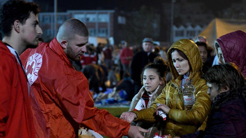 People receive food as they take shelter in a camp at the soccer stadium in Durres on November 26, 2019, after the strongest earthquake in decades